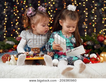 two girls unpack gifts in christmas decoration, dark background with illumination and boke lights, winter holiday concept