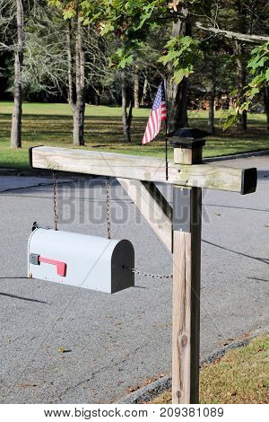 Rural mailbox post holding a small American flag.