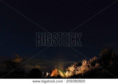 tent under the stars at night bonfire