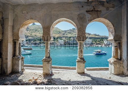 View to Balaklava bay through arched balcony in oriental style. Abandoned mansion on Black Sea coast