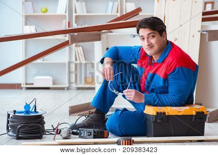 Young carpenter taking break from working with wooden planks