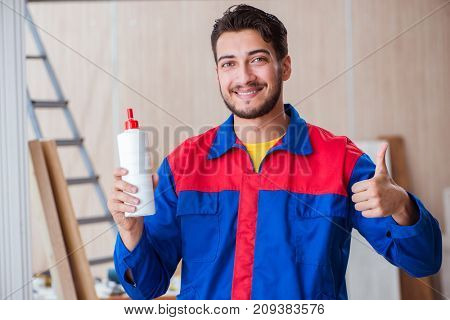 Yooung repairman carpenter working with paint painting