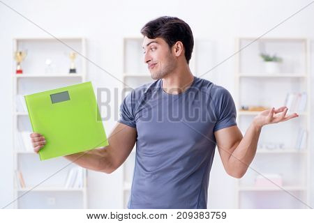 Man with scales in sports and health concept