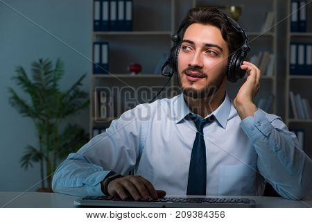 Young man in call center concept working late overtime in office
