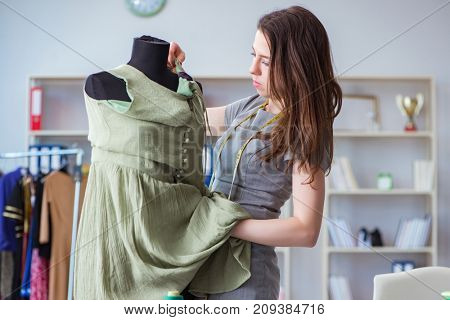 Woman tailor working on a clothing sewing stitching measuring fa