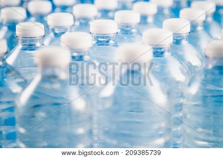 Side view of plastic water bottles in a row. Concept of factory production, recycling, disposal of waste, and environmental conservation.