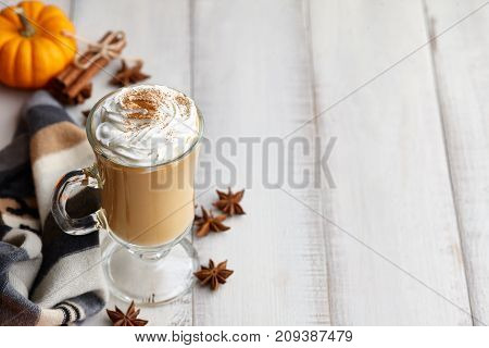 Fall pumpkin spice latte with whipped cream and cinnamon, ornamental pumpkins and warm woolen scarf on white wooden background, copyspace