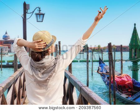 Young female traveler on pier enjoying beautiful view on venetian chanal with gondolas floating in Venice, Venice