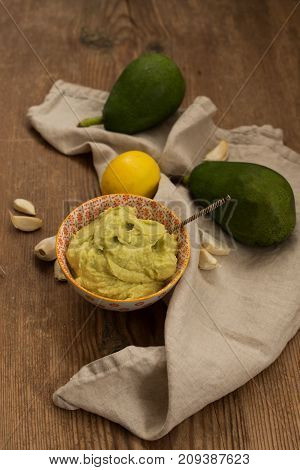 avocado sauce in a small bowl with entic pattern  and one lemon, two avocados and a few pieces of garlic placed over wooden rustic background