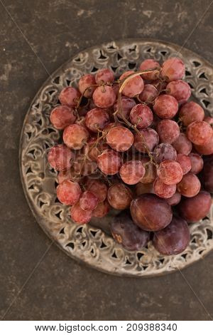 Vertical upper view shot of grapes and plums on iron vintage plate over dark gray rustic background
