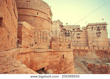 Great towers of historical Jaisalmer fort with monumental stone walls over the old city, India.