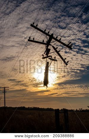 Destroyed power line. Abandoned power line. Sunset in the field