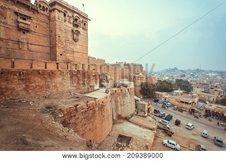 Many cars parking past the historical Jaisalmer fort with stone towers in Thar desert, Rajasthan of India