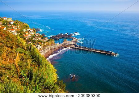 The picturesque village with tiled roofs on the cape is surrounded by forest. The magical tropical island of Madeira. Concept of exotic and ecological tourism