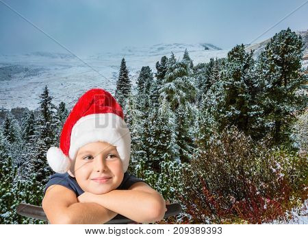 Pine forest in mountains are covered with the first snow. Charming eight-year boy in Santa Claus hat thinking