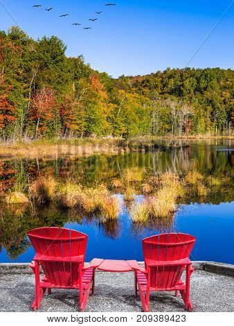 Red plastic loungers on the shore of the pond. Flock of migratory birds flies over the lake. Magnificent resort in French Canada - Mont Tremblant. Concept of ecological tourism
