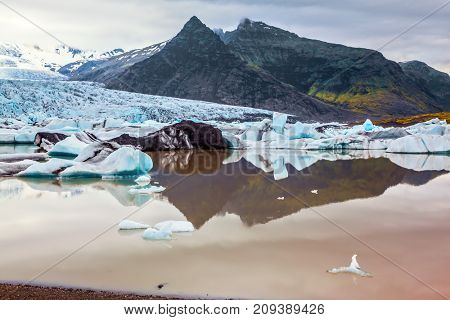 Grandiose glacier of Iceland Vatnajokull in beams of a summer sunset. The concept of extreme northern tourism. Glacier provides water Ice Lagoon Jokulsarlon