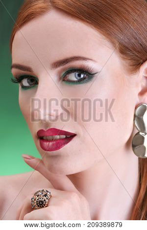 Beautiful redhead woman with bright green makeup on green background, closeup