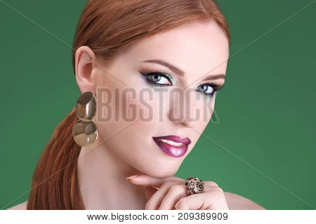 Beautiful redhead woman with bright green makeup on green background
