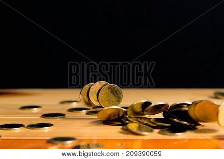Falling Gold Coins Money On Wooden Table With Black Wall, Copy Space, Business Wealth Concept.