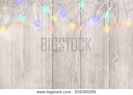 Twinkling Christmas Lights Top Border, Above View On A Light Gray Wood Background
