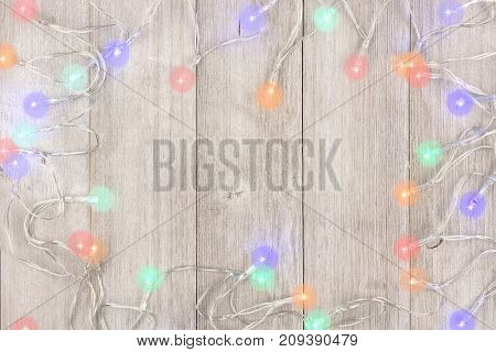 Twinkling Christmas Lights Frame, Above View On A Light Gray Wood Background