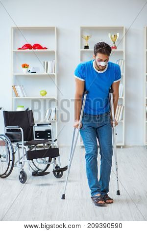 Young man recovering after surgery at home with crutches and a w