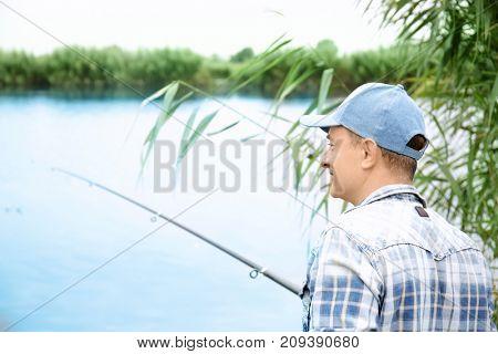 Man fishing on riverside