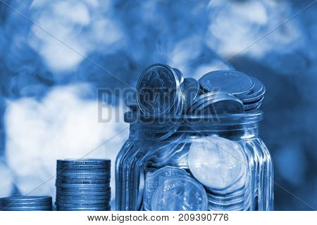 Step Of Coins Stacks And Gold Coin Money In The Glass Jar On Table In Garden With Green Background,