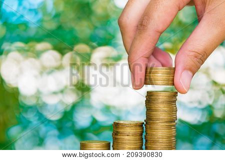 Woman Hand Put Coin On Step Of Coins Stacks And Gold Coin Money In The Glass Jar On Table In Garden