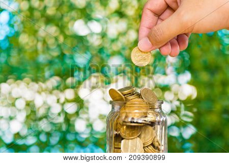 Woman Hand Put Gold Coin Money In The Glass Jar On Table In Garden With Green Background, For Saving