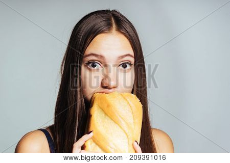 a hungry girl is on a diet, eagerly eats harmful white bread