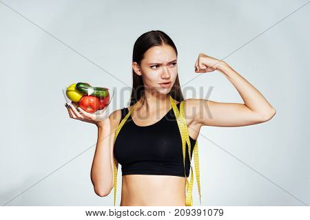the sports young girl watches her figure, holds a plate with vegetables and fruits, shows her bicep