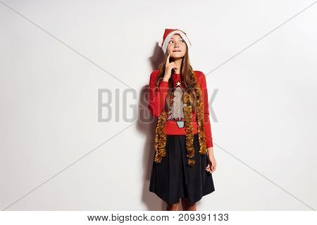 the girl thought about the new year and Christmas, dreamily looks up, in a red cap and gold tinsel