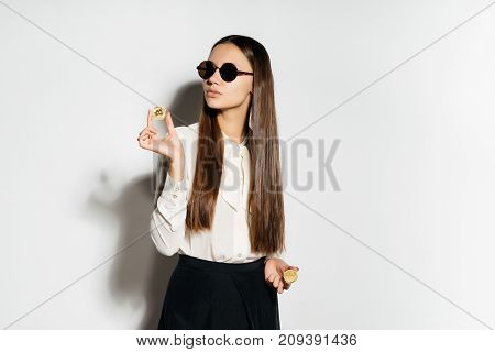 young business woman in sunglasses understands the crypto currency and holds a golden bitcoin in hands
