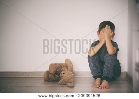 Scared little boy sitting in corner of room. Domestic violence concept
