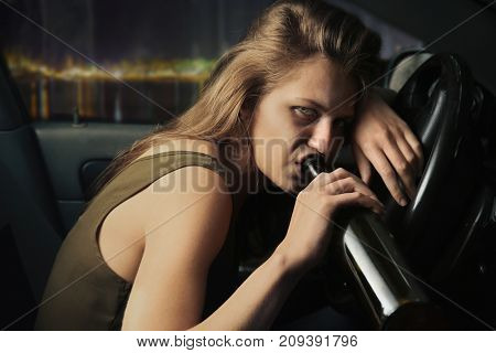 Woman drinking alcohol in car