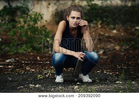 Drunk woman sitting with cigarette and bottle of alcohol outdoors