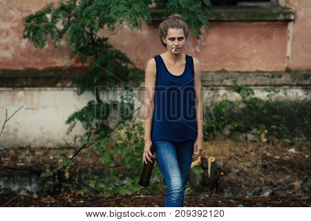 Drunk woman with cigarette and bottle of alcohol outdoors