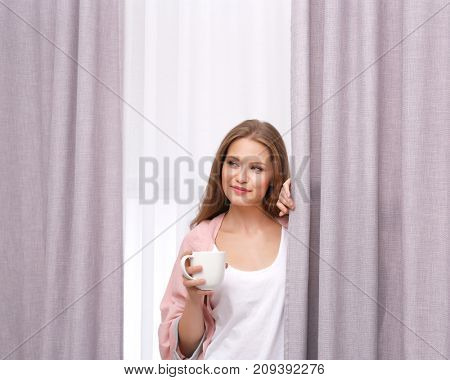 Young woman with cup of coffee standing near curtains at home