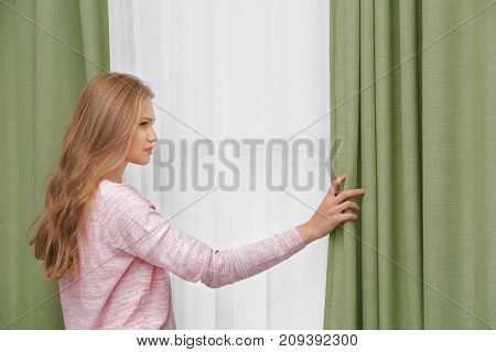 Young woman opening curtains at home