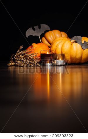 for the scenery of the house for Halloween, lie yellow and orange pumpkins, lighted candles and drawings of bats