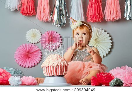 Little baby girl eating birthday cake during cake smash party