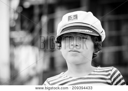 Portrait of a boy in a striped long sleeve T-Shirt (Telnyashka) and captain's cap. Black and white.