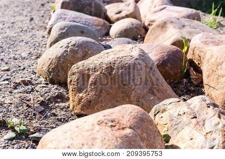 border of stones near the walkway. nature peace.