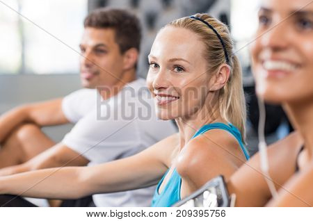 Portrait of young woman sitting at gym. Smiling blonde woman in sportswear doing exercises with friends at fitness studio. Happy girl with ponytail resting after workout.