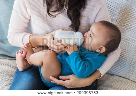 Little infant baby lying on mothers hand drinking milk from bottle. Newborn baby drinking milk from bottle. Cute toddler with milk bottle on leg of mother.
