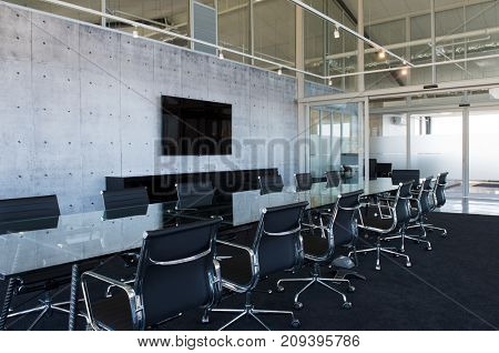 Chairs and table in the boardroom in office. Business elegant meeting room. Interior of a modern office empty meeting room with crystal table, black leather chairs and a television on grey wall.