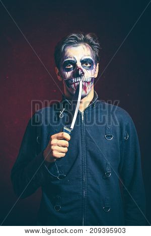 scary halloween skeleton man in jacket hold big knife studio shot
