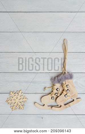 Christmas and New Year holiday background. Close up handmade ornaments of skate and snowflake on wooden table, festive decoration and celebration concept. flat lay top view